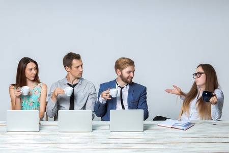 Photo for Business team working on their business project together at office on light gray background.  all drinking coffee and looking at the boss. copyspace image. - Royalty Free Image