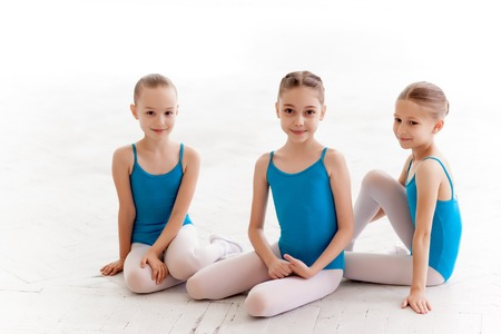Photo for Three little ballet girls sitting in blue swimsuit and pointe shoes together on white background in ballet studio - Royalty Free Image
