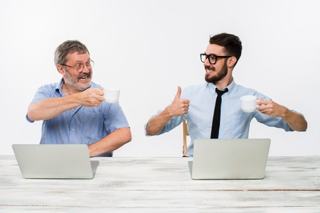 Foto de The two colleagues working together at office on white  background. both happy men are getting good news. concept of  success in business. they rejoicing and clinking cups - Imagen libre de derechos