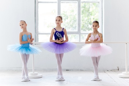 Photo for Three little ballet girls in multicolored tutu posing at ballet barre together in white studio - Royalty Free Image