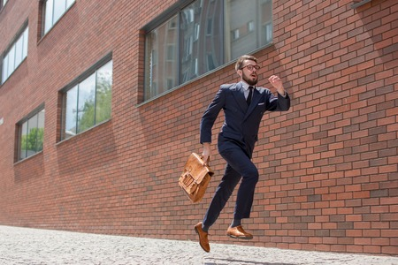 Foto de Young businessman with a briefcase and glasses running in a city street on a background of red brick wall - Imagen libre de derechos