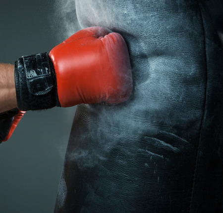 Close-up hand of boxer at the moment of impact on punching bag over black background