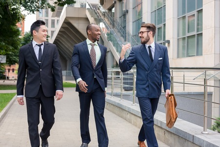 Photo for Portrait of multi ethnic business team.Three smiling men walking against the background of city. The one man is European, other is Chinese and African-American. - Royalty Free Image