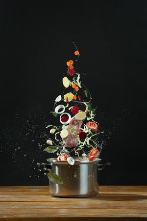 Foto de Fresh vegetables falling into a stainless steel casserole on wooden table. The concept of cooking borsch - Imagen libre de derechos