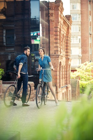 Young couple sitting on a bicycle opposite the green city park