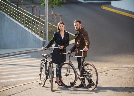 Young couple with a bicycle opposite the city