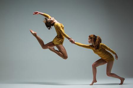 Photo pour The two modern ballet dancers dancing on gray background - image libre de droit