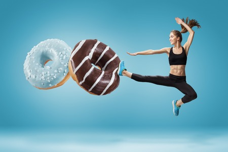 Photo for Fit young woman fighting off bad food on a  blue background. Concept of diet and healthy lifestile - Royalty Free Image