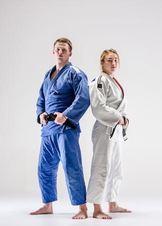 Foto de The two judokas fighters posing on gray - Imagen libre de derechos