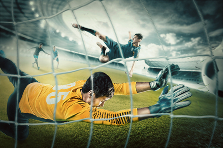 Photo pour Goalkeeper in gates jumping to catching ball - image libre de droit