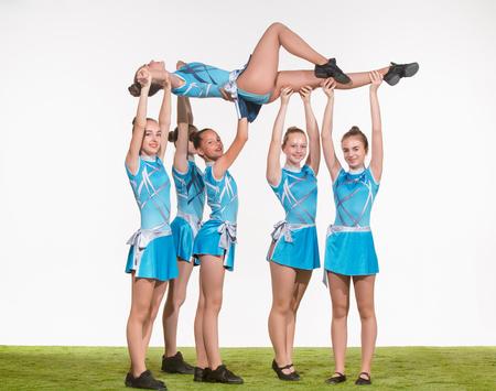 Foto de The group of teen cheerleaders posing at white studio - Imagen libre de derechos