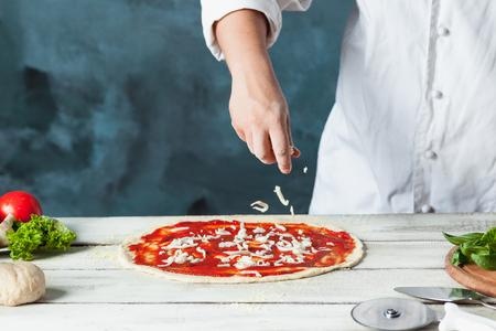 Photo pour Closeup hand of chef baker in white uniform making pizza at kitchen - image libre de droit