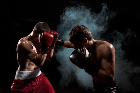 Photo pour Two professional boxer boxing on black smoky background, - image libre de droit