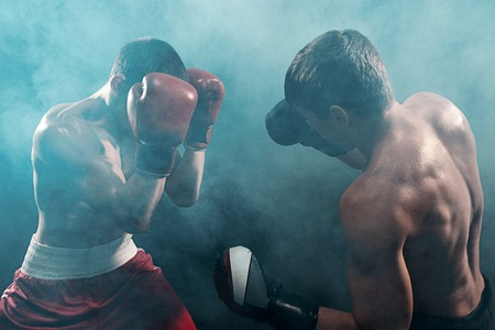 Foto de Two professional boxer boxing on black smoky background, - Imagen libre de derechos