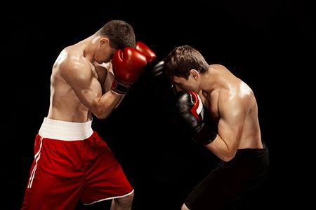 Foto de Two professional boxer boxing on black background, - Imagen libre de derechos