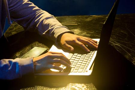 Foto de Hooded computer hacker stealing information with laptop - Imagen libre de derechos