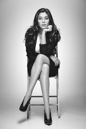 Photo pour The colorless portrait of business woman sitting on chair in studio - image libre de droit