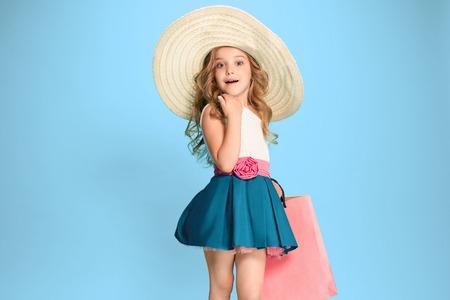 Foto de The cute little caucasian brunette girl in dress holding shopping bags - Imagen libre de derechos