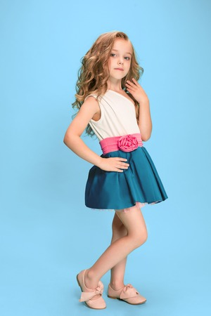 Photo pour Full length of beautiful little girl in dress standing and posing over blue background - image libre de droit