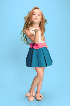 Photo for Full length of beautiful little girl in dress standing and posing over blue background - Royalty Free Image