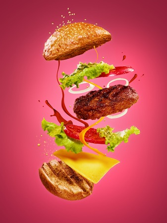 Photo for The hamburger with flying ingredients on rose background - Royalty Free Image