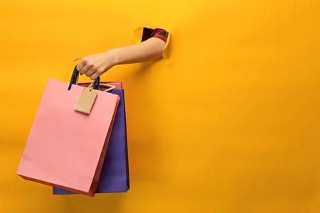 Photo pour Female hand holding bright shopping bags - image libre de droit