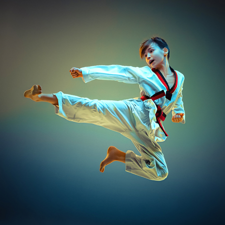 Foto de Young boy training karate on blue background - Imagen libre de derechos