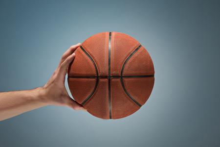 Photo pour Low key shot of a hand holding a basket ball - image libre de droit