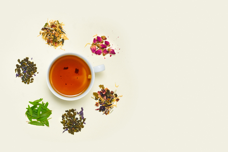 Photo for Cup of tea, placer of dry fruit tea and dry flowers on white background, top view - Royalty Free Image