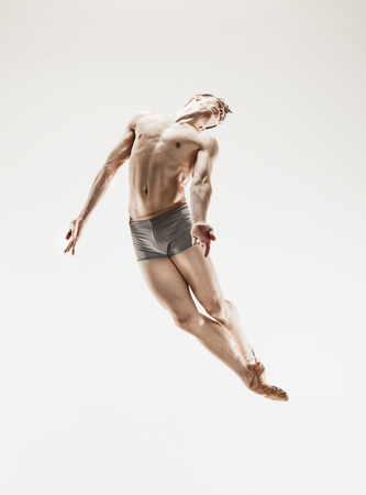 Foto de The male athletic ballet dancer performing dance isolated on white background. - Imagen libre de derechos