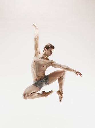 Foto de The male athletic ballet dancer performing dance isolated on white background. - Imagen libre de derechos