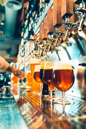 Foto de Hand of bartender pouring a large lager beer in tap. - Imagen libre de derechos