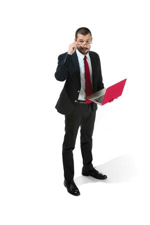 Foto de Picture of handsome young bearded man standing over white studio background with laptop - Imagen libre de derechos
