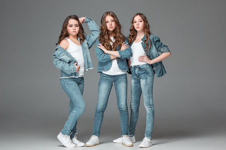 Photo for The fashion girls standing together and looking at camera over gray studio background - Royalty Free Image