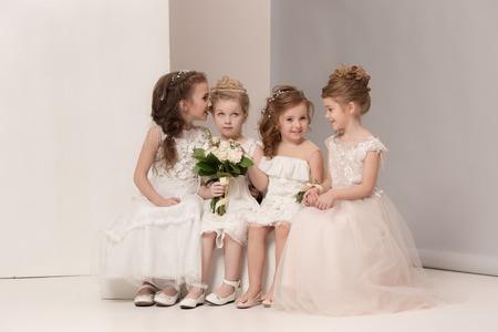 Photo pour Little pretty girls with flowers dressed in wedding dresses - image libre de droit