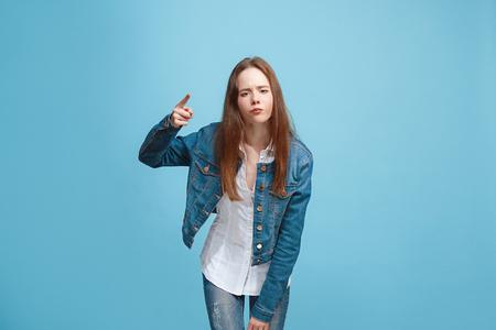 Foto de Beautiful female half-length portrait on blue studio backgroud. The young emotional teen girl - Imagen libre de derechos