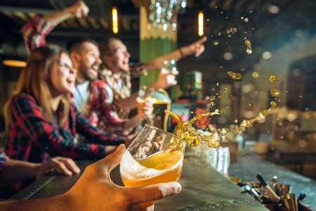 Photo pour sport, people, leisure, friendship and entertainment concept - happy football fans or male friends drinking beer and celebrating victory at bar or pub - image libre de droit