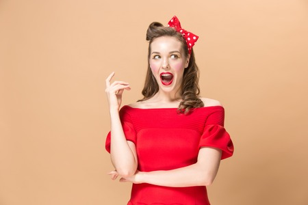 Photo pour Beautiful young woman with pinup make-up and hairstyle. Studio shot on pastel background - image libre de droit