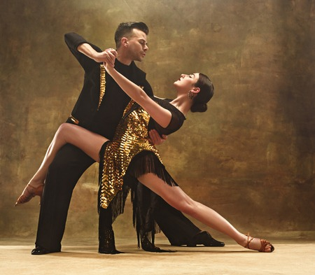 Photo pour Dance ballroom couple in gold dress dancing on studio background. - image libre de droit