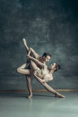 Foto de The young modern ballet dancers posing on gray studio background - Imagen libre de derechos