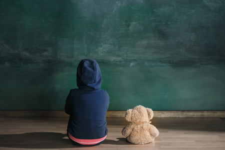 Foto de Little girl with teddy bear sitting on floor in empty room. Autism concept - Imagen libre de derechos