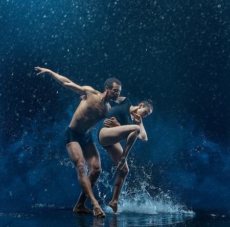 Foto de Young couple of ballet dancers dancing unde rwater drops - Imagen libre de derechos