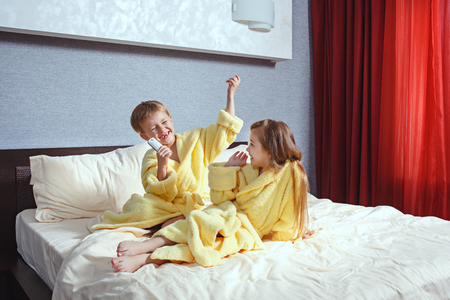 Photo pour Happy laughing kids, boy and girl in soft bathrobe after bath play on white bed - image libre de droit