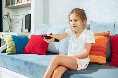 Photo pour Little casual girl watching tv at home. Female kid sitting on sofa with TV remote and switching channels - image libre de droit