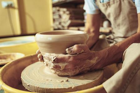 Photo pour Creating a jar or vase of white clay close-up. Master crock. Man hands making clay jug macro. - image libre de droit