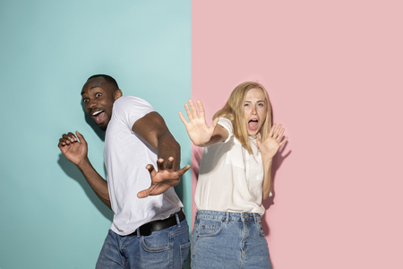 Photo for Portrait of the scared couple on pink and blue studio background - Royalty Free Image