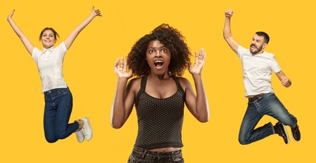 Photo for Wow. Beautiful female half-length portrait isolated on gold studio backgroud. Young surprised woman and jumping running man isolated on yellow. Human emotions, facial expression concept. Trendy colors - Royalty Free Image