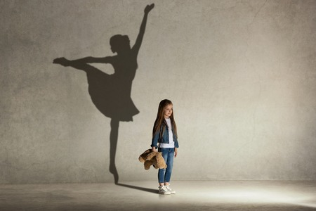 Photo pour Baby girl dreaming about dancing ballet. Childhood and dream concept. Conceptual image with shadow of ballerina on the studio wall - image libre de droit