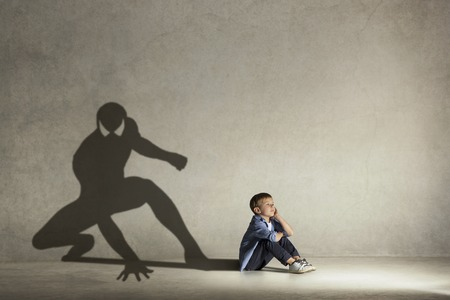 Photo pour The little boy dreaming about hero figure with muscles. Childhood and dream concept. Conceptual image with boy and shadow of fit athlete on the studio wall - image libre de droit