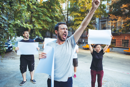 Foto de Group of protesting young people outdoors. The protest, people, demonstration, democracy, fight, rights, protesting concept. The caucasian men and womem holding empty posters or banners with copy space - Imagen libre de derechos